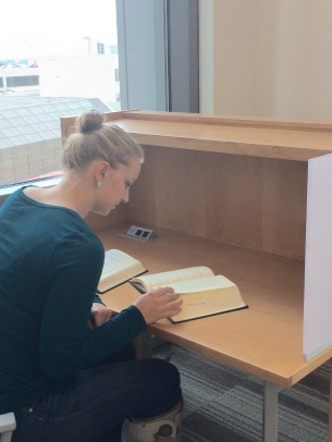 student reading a book in a study carrel in the law library.