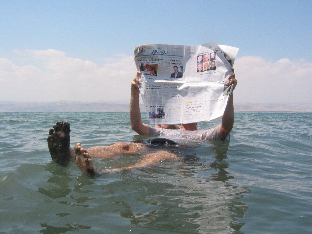 Person reading newspaper while floating in the ocean.